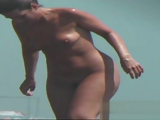 Sexy toned body walking naked on a crowded beach